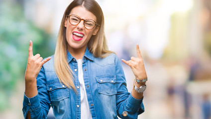 Young beautiful woman over wearing glasses over isolated background shouting with crazy expression doing rock symbol with hands up. Music star. Heavy concept.