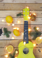 Photo shot, top view of yellow ukulele, lemons and new year symbols on wooden background.