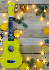 Photo shot of yellow ukulele, lemons and new year symbols on wooden background.