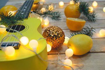 Photo of yellow ukulele, lemons and new year symbols on wooden background.