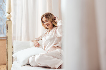 selective focus of smiling woman in pajama posing in bed during morning time at home
