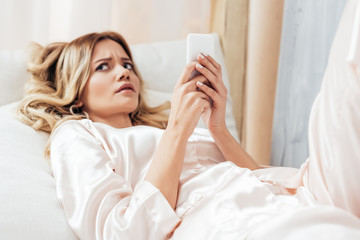 irritated young woman using smartphone in bed during morning time at home