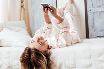 smiling girl using smartphone in bed during morning time at home
