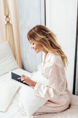 smiling blonde woman in pajama using digital tablet with blank screen in bed during morning time at home