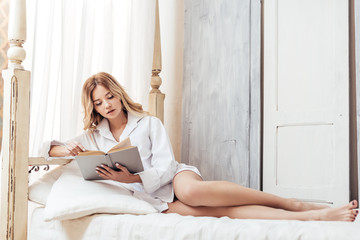 attractive girl reading book in bed during morning time at home