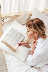 high angle view of blonde girl in pajama reading book in bed during morning time at home