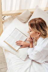 high angle view of girl in pajama reading book in bed during morning time at home