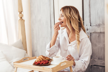 happy woman having breakfast with coffee, croissant and raspberries in bed at home
