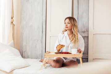 beautiful woman having breakfast with coffee, croissant and raspberries in bed at home