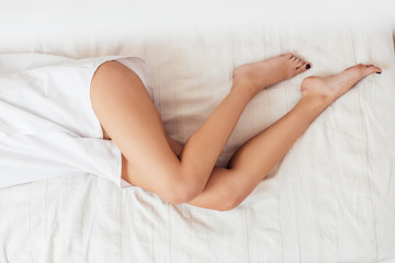 low section of young woman with naked legs laying in bed at home