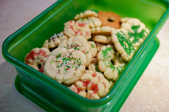 Homemade butter spritz Christmas cookies packed in a green plastic container for easy transport to a party