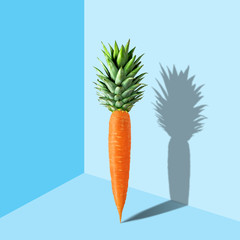 Carrot with pineapple leaves on pastel blue background. Easter minimal concept.
