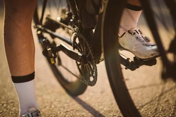 Professional road bicycle racer posing. Men cycling mountain road bike at sunset.