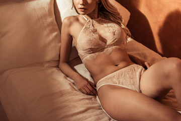 partial view of seductive female model wearing sexy beige lingerie and posing in bed