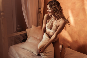 happy blonde girl in lace lingerie posing with pillows in bed