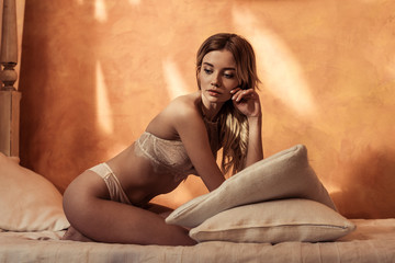 girl in seductive lace lingerie posing with pillows in bed