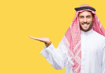 Young handsome man wearing keffiyeh over isolated background smiling cheerful presenting and pointing with palm of hand looking at the camera.