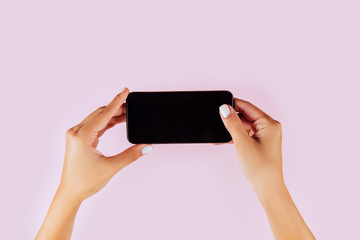 Woman Hand holding smartphone on pink background
