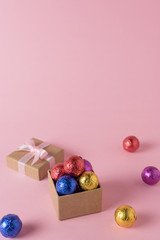 Creative layout of colored candy and gift box on pink background. Minimal holiday concept.