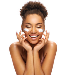 Happy young girl with moisturizing cream on her face. Photo of smiling african american girl isolated on white background. Skin care and beauty concept