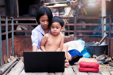Asian uniform student girl and her brother using computer notebook in countryside of Thailand