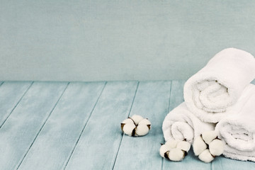 Rolled up white fluffy towels with cotton flowers against a blurred blue background with free space for text