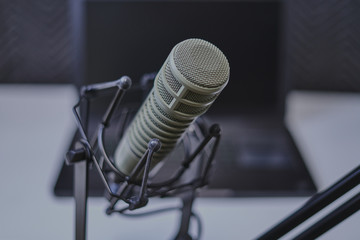 Podcast recording microphone with laptop