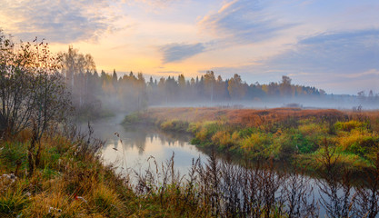 Foggy autumn landscape with small forest river.Autumnal hazy early morning.Twilight.Calm stream of river flowing between the woods and meadows covered by fog.Colorful clouds in sky at sunrise.
