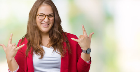 Beautiful plus size young business woman wearing elegant jacket and glasses over isolated background shouting with crazy expression doing rock symbol with hands up. Music star. Heavy concept.