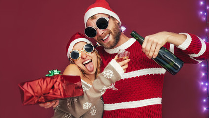Happy crazy couple cheering with champagne at christmas party - Teenager young people having fun drinking and celebrating xmas holidays - Concept of millennial, love, fest and youth lifestyle
