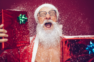 Happy crazy santa claus holding christmas box gifts - Hipster sanior man having fun laughing and wearing xmas winter costume - Concept of people doing funny celebration of x-mas holidays