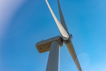 Contre-plongée d'une éolienne sur fond de ciel bleu