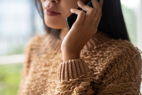 Close-up of lady using mobile phone for important communication. Serious busy woman in sweater talking on cellphone. Business concept