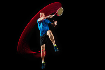 The one caucasian man playing tennis isolated on black background. Studio shot of fit young player at studio in motion or movement during sport game with led light trail