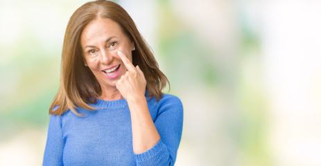 Middle age beautiful woman wearing winter sweater over isolated background Pointing to the eye watching you gesture, suspicious expression