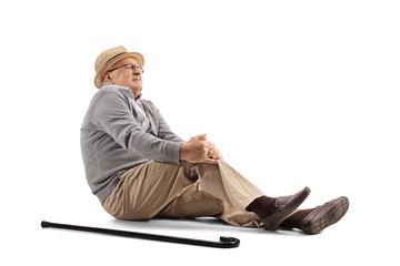 Mature man lying on the floor and holding his knee