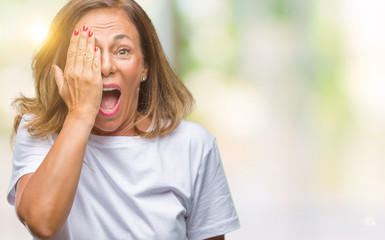 Middle age senior hispanic woman over isolated background covering one eye with hand with confident smile on face and surprise emotion.