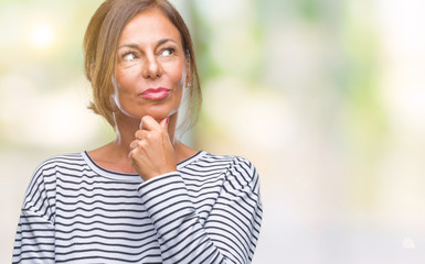Middle age senior hispanic woman over isolated background looking confident at the camera with smile with crossed arms and hand raised on chin. Thinking positive.