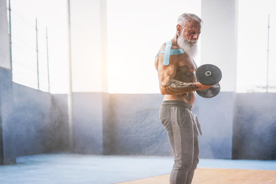 Fitness beard man doing biceps curl exercise  inside a gym - Tattoo senior man training with dumbbells in wellness club center - Body building and sport fit concept