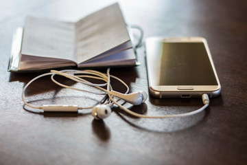 Phone next to a pair of earphones.