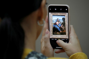 """A visitor takes a picture of the painting """" The Virgin and Child with Saint Anne """" by Leonardo Da Vinci at the Louvre museum in Paris"""