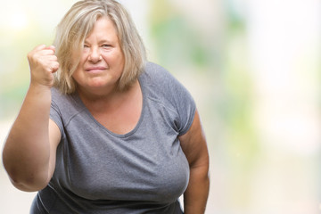 Senior plus size caucasian woman over isolated background angry and mad raising fist frustrated and furious while shouting with anger. Rage and aggressive concept.