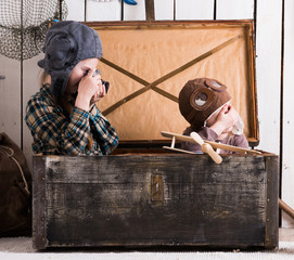 two little girls in hats playing in big wooden chest with old camera