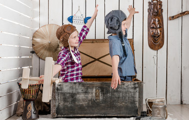 two little children-pilots fly with hands sitting in big old chest