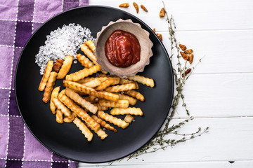 Plate of homemade french potatoes with ketchup and sea salt on plaid napkin and white wooden background, top view