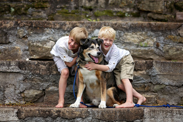 Two Happy Little Boy Children are Lovingly Hugging their Adopted Family Dog