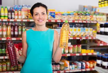 Woman choosing different oil in bottle