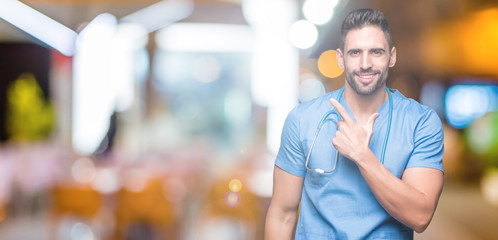 Handsome young doctor surgeon man over isolated background cheerful with a smile of face pointing with hand and finger up to the side with happy and natural expression on face