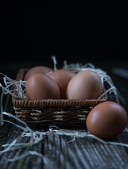 chicken eggs in a purse on a dark background. Low key. Rustic. Close up, selective focus. Copy space