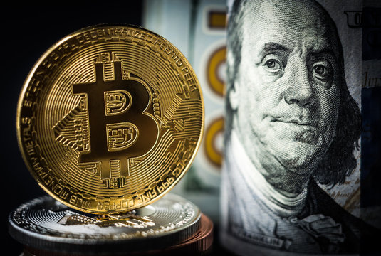 Gold bitcoin coin standing in front of dollar bills. New virtual money concept
